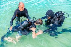 A man in a suit for diving prepares a boy to dive. A men in a suit for diving prepares a boy to dive stock image
