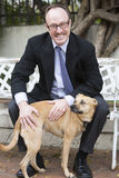 Man in suit with a dog. Man in a suit sitting outside with a dog Stock Image