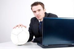 Man in suit dreaming thinking about football socce. Handsome charming businessman in suit with ball dreaming thinking about football soccer near computer in Royalty Free Stock Photography