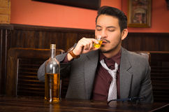 Man in suit drinking alcohol shot Royalty Free Stock Photo