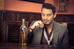 Man in suit drinking alcohol shot Stock Photos
