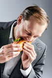 Man in suit eats BLT eagerly. Hungry man in business suit devours BLT baguette with big greedy bite Royalty Free Stock Photos
