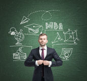 Man in suit and education icons on blackboard Stock Photography
