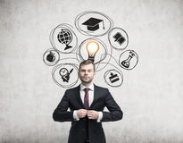 Man in suit and education icons on concrete. Businessman buttoning his suit is standing near a concrete wall with education icons and a light bulb stock image