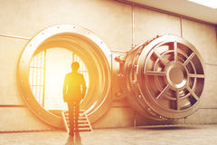 Man in suit entering the sunlit vault. Rear view of man in suit entering the sunlit vault of the bank. Concept of bank employee. 3d rendering royalty free stock photography