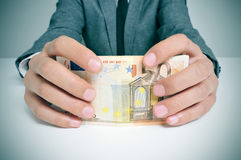 Man in suit with euro bills. Man in suit in a office desk with a wad of euro bills in his hands Stock Image