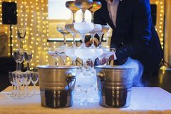 Man in suit fills the 4-tier champagne tower with sparkling wine at the illuminated banquet hall background. The glasses tower wit royalty free stock image