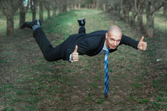 Man in a suit flying the park. Stock Photo