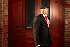 Man in suit in front of old doors. A young man in a suit with a red tie and hat standing in front of wooden doors Royalty Free Stock Photos