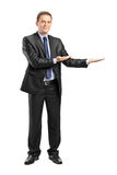 Man in suit gesturing welcome. Full length portrait of a man in suit gesturing welcome on white background Royalty Free Stock Images