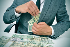 Man in suit getting dollar bills in his jacket Royalty Free Stock Photo