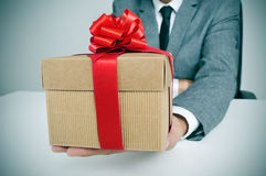 Man in suit with a gift Stock Images