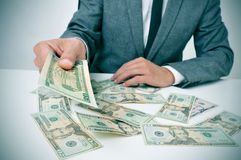 Man in suit giving dollar bills Stock Image