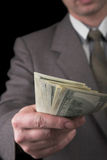 Man in suit giving dollars. Isolated on black Royalty Free Stock Photos