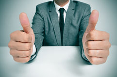 Man in suit giving a thumbs up signal. Man wearing a suit sitting in a table giving a thumbs up signal Stock Photo