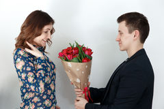 Man in suit giving tulip bunch to young woman Stock Photo
