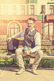 Man in suit with glasses and whiskers holding book in the old town. While sitting on bench in park posing, vintage and retro effect in picture stock photos