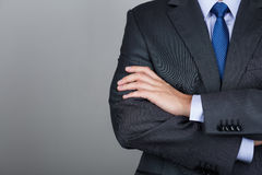 Man in suit in gray background. Business man with folded hands against gray background. Copy space Royalty Free Stock Image