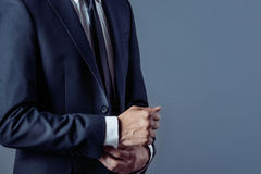 Man in suit on a grey background, hands closeup Royalty Free Stock Photography