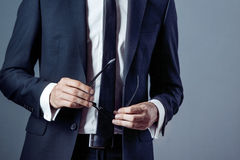 Man in suit on a grey background, hands closeup Stock Photos