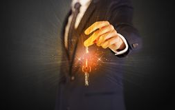 Man in suit hand over keys Stock Photography