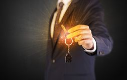 Man in suit hand over keys Royalty Free Stock Photo
