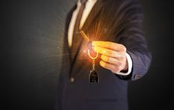 Man in suit hand over keys Royalty Free Stock Photography