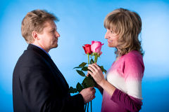 She and He. The man in a suit has presented the bouquet of flowers Royalty Free Stock Photography