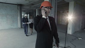 Man in suit, helmet call inside construction site. At background team of young builders man, african. American and woman discuss plan of project, communicate stock footage