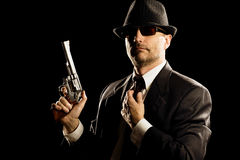 Man in suit holding a 357 magnum revolver. Photo of man shot with studio lighting, holding a handgun, with Fedora Hat, Dark Suit and Sun Glasses stock images