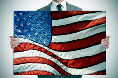Man in suit holding an american flag royalty free stock images