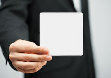 Man in suit holding blank card Stock Images