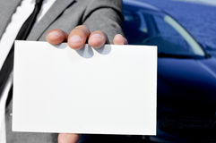 Man in suit holding a blank signboard with a car in the backgrou Royalty Free Stock Photos