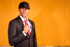 Man in suit holding coat by wall. A young man in a suit with a red tie and hat standing in front of a yellow wall Stock Photography