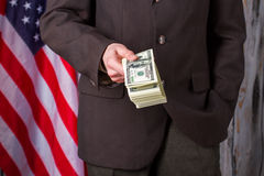 Man in suit holding dollars. Stock Photo