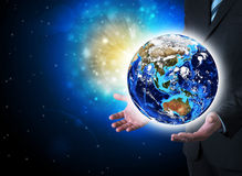 Man in suit holding a earth in hand Stock Photography