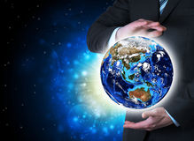 Man in suit holding a earth in hand Stock Images