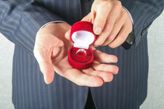 Man in suit holding engagement ring Stock Photos