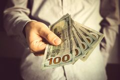 Man in a suit holding fan of dollar banknotes Royalty Free Stock Photos