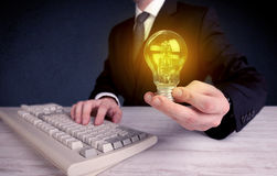 Man in suit holding a glowing yellow light bulb Stock Images