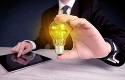 Man in suit holding a glowing yellow light bulb Stock Photos