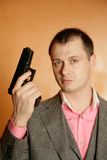 Man in suit holding gun. Man in grey suit standing on orange background holding up gun Stock Photo
