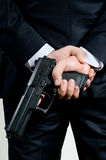 Man in suit holding gun. Man in black suit holding gun Royalty Free Stock Photography