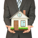 Man in suit holding house Royalty Free Stock Images