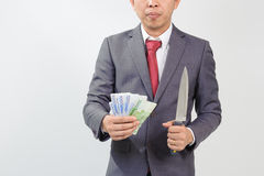 Man in suit holding knife and korean won Stock Photo
