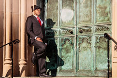 Man in suit holding leaning on building. A young man in a suit with a red tie and hat leaning on building Royalty Free Stock Photo