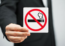 Man in suit holding no smoking sign Stock Photo