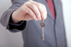 Man in suit holding out key Royalty Free Stock Image