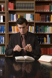 Man In Suit Holding Pen Over Book At Library Desk Royalty Free Stock Photography