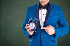 Man in suit holding and point to the clock Royalty Free Stock Photography